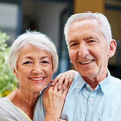 Old Couple Smiling After Dental Implant Restorations