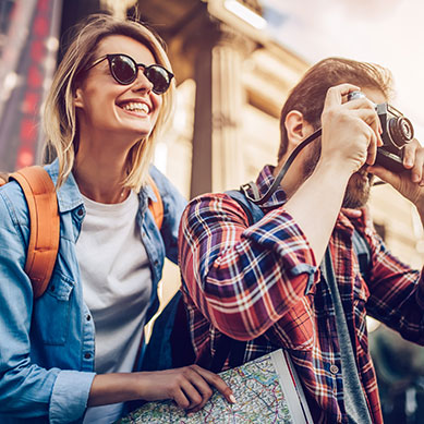 Young Traveling Couple Taking Photos And Smiling