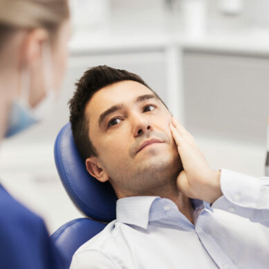 male patient with toothache complaining to female dentist at dental clinic office