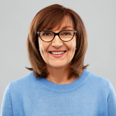 portrait of smiling senior woman in glasses over grey background