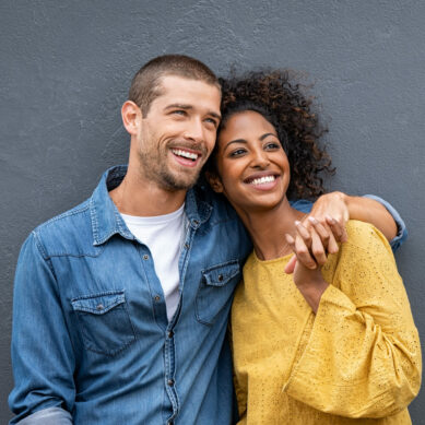 Smiling man and african woman in casual hugging and looking away while planning the future