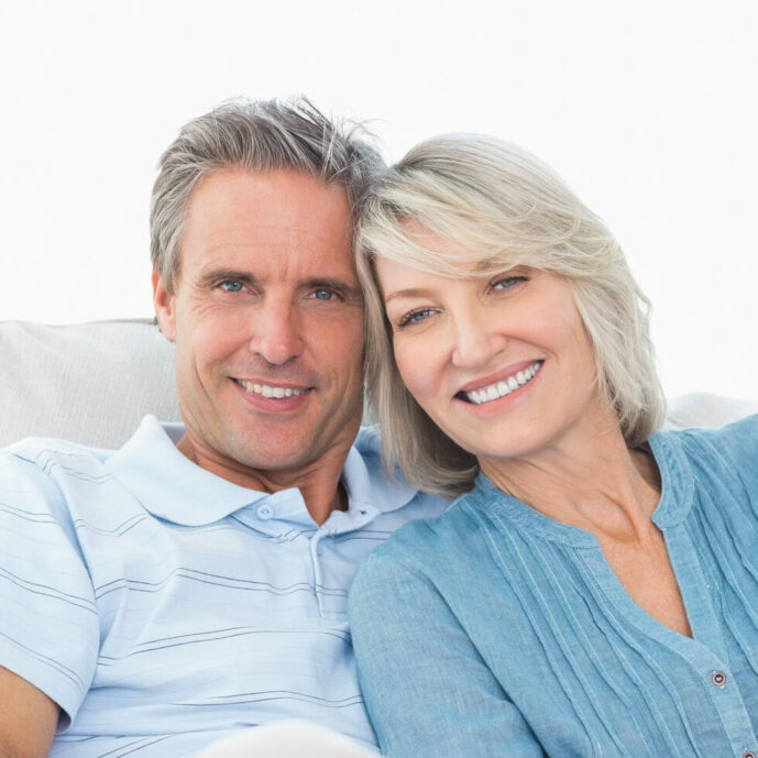 Cheerful couple on their couch smiling at camera at home