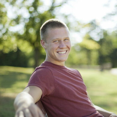 Handsome young man sitting on a bench in the Park smiling